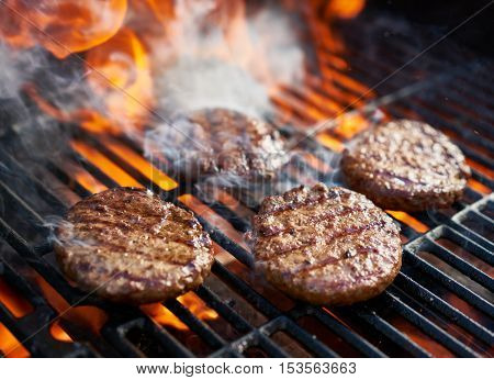cooking burgers on hot grill with flames