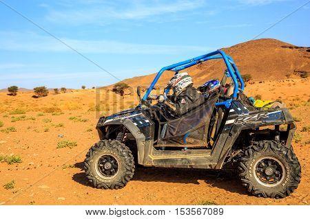 Merzouga, Morocco - Feb 26, 2016: Blue Polaris Rzr 800 And Pilots In Morocco Desert Near Merzouga. M