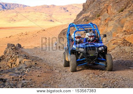 Merzouga, Morocco - Feb 21, 2016: Blue Polaris Rzr 800 And Pilots Crossing On A Mountain Road In Mor