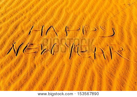 Happy new year written in the sand of the desert