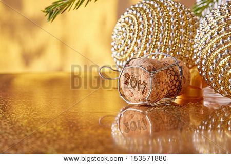 Cork from the champange, fir tree branch and christmas decoration on a golden background. New year and Christmas.