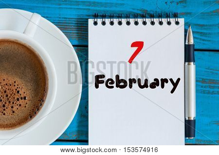 February 7th. Day 7 of month, calendar in notepad on wooden background near morning cup with coffee. Winter time. Empty space for text.