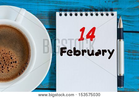 February 14th. Day 14 of month, calendar in notepad on wooden background near morning cup with coffee. Winter time. Empty space for text.