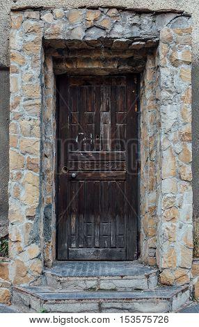 Dark wooden door entrance masonry around stage