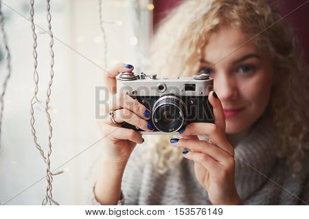 Young blond curly female in warm sweater with old film camera smiling and shooting a photo in the cafe winter city outside the window