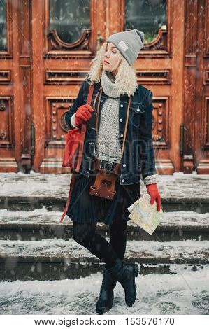 Young blond curly female in warm clothes with old film camera and map standing. Wooden doors with handles on the background winter