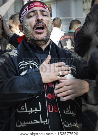 Istanbul Turkey - October 11 2016: Shia Muslim men shout Islamic slogans as they mourn during an Ashura procession. Muslims worldwide marks Ashura Istanbul Shiite community. Turkish Shia Muslims mourning for Imam Hussain. Caferis take part in a mourning p