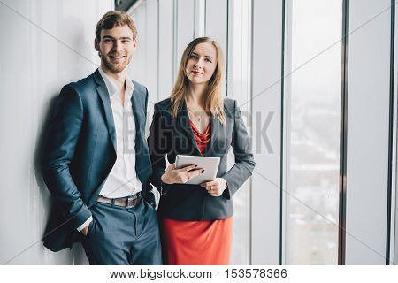 Group of business people a man in a suit and a woman in a red dress and jacket holding a tablet winter city landscape outside the window on the background