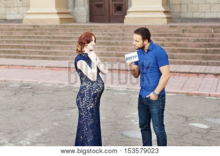 Funny image. Сouple expecting a baby: man holds a sign saying