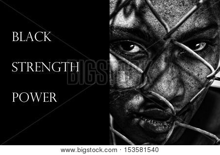 Image of a afro American woman behind a fence, depicting Racism,Strength and Power