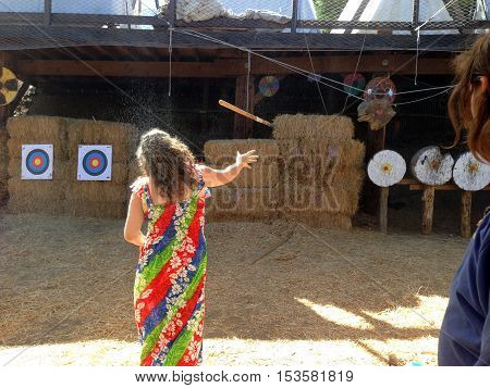 A Woman Throws A Spear At A Target During the Viking Festival While The Instructor Looks On