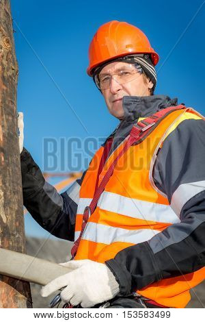 RUSSIA - OCTOBER 19: Electrician lineman repairman worker at climbing work on electric post power pole