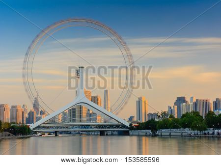 Cityscape of Tianjin ferris wheelTianjin eyes in evening time with long exposure effect. Most popular modern tourist attraction in Tianjin city China.
