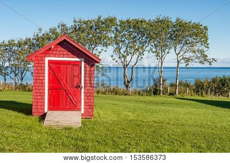 Red shed with blue sky and green grass in Gaspe Peninsula Quebec Canada