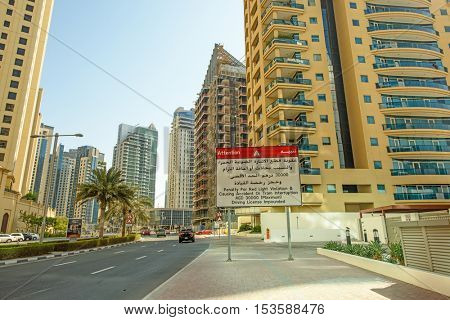 DUBAI, UAE - OCTOBER 07, 2016: A tram violation sign in Dubai Marina Jumeirah Beach Residence.  Surrounded by tall unique skyscrapers with apartments and restaurants, the marina is open to The Gulf.