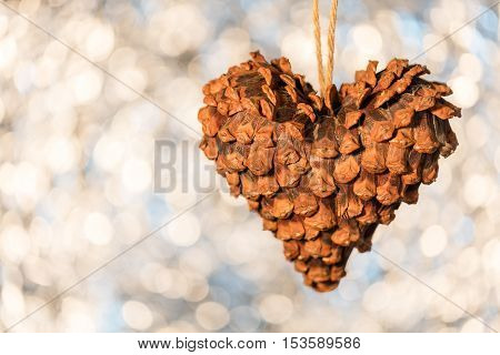 Pinecone Christmas decoration in shape of heart on sparkling bokeh background shallow depth of field