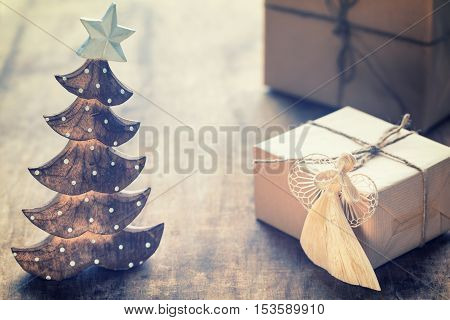 Christmas Composition with present box wooden Christmas tree festive decorations on wooden background. Rustic stile.