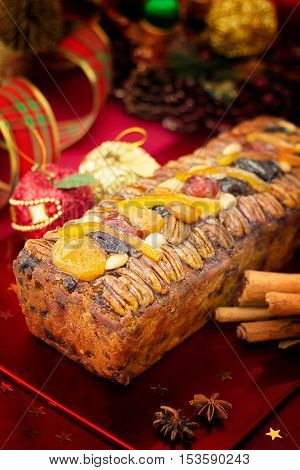 Traditional Christmas fruit cake with festive decorations and Xmas spices on red background.Vertical compositon