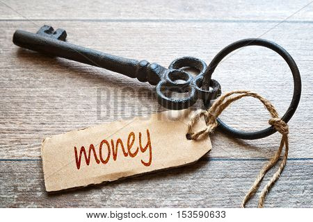 Keys to Money - Concept photo. Old key with paper label on wooden background - Money text.