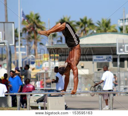 Venice Beach, California, 10/15/16--Athletic male gymnast does a handstand on dip bars at Muscle Beach outdoor gym.