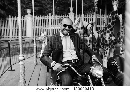 Man sitting at motorcycle on merry go round carousel