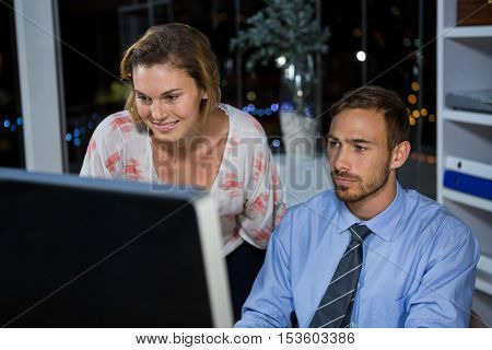 Business executives working on computer in office at night