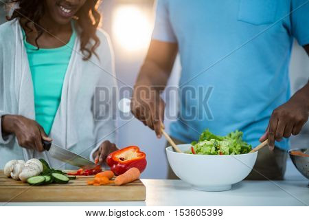 Mid-section of couple preparing food in kitchen
