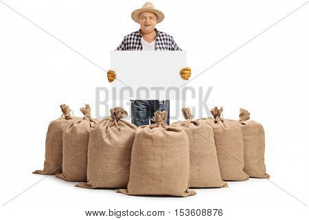 Elderly farmer standing behind burlap sacks and holding a blank signboard isolated on white background