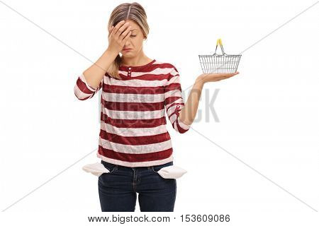 Young woman with empty pockets holding her head in disbelief and holding a small empty shopping basket isolated on white background