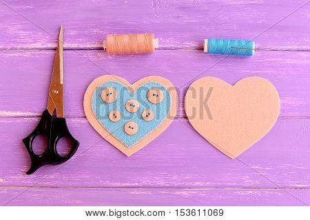 How to make a felt heart crafts. Step. On one side of the felt heart buttons sewn using blue thread. Scissors, thread, needle on wooden background. Souvenir for Valentine's day, wedding, mother's day