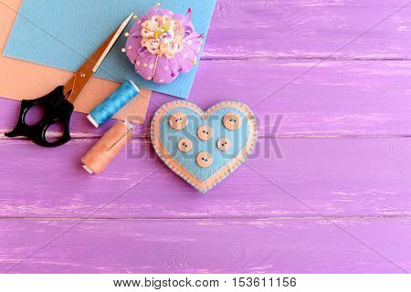 How to make a felt heart crafts. Step. Decorative felt heart, scissors, thread, needle, felt sheets, pincushion, pins on wooden background. Crafts project for Valentine's day, wedding, mother's day