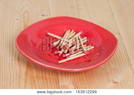 Matchsticks in red plate over wooden background