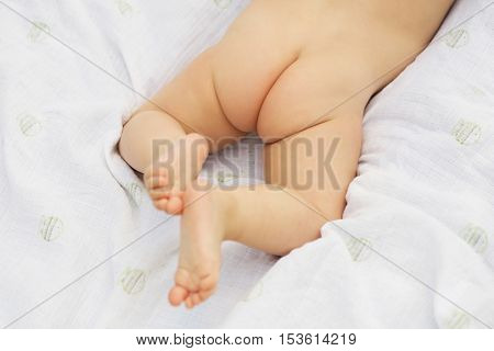 Naked baby's bottom and legs. Child take air baths