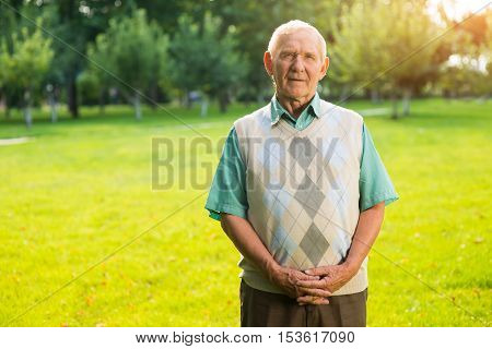Senior man standing outdoors. Older male on nature background. I recall faces and names. Thoughts and guesses.