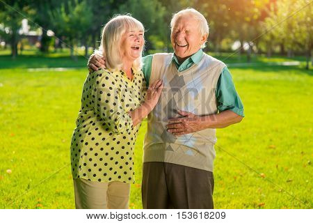 Couple of seniors laughing. Old people outdoors. Not a day without laughter. Look at everything with humor.