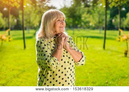 Woman clasping hands on chest. Smiling elderly lady outdoors. All my hopes and dreams. Life is full of wonders.