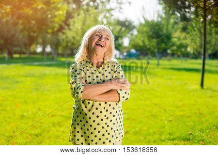 Senior woman laughing. Lady with crossed arms outdoor. Beauty doesn't get old. Joy in the heart.