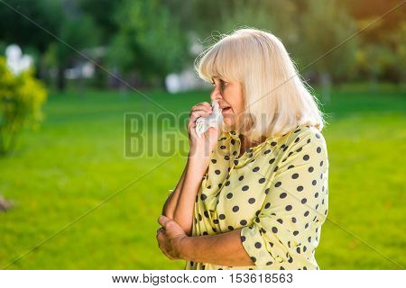 Elderly woman crying. Older lady outdoors. My heart is broken. Fate is cruel.