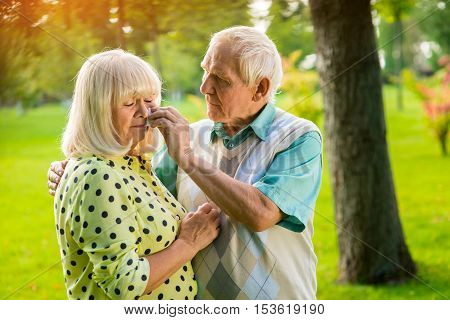 Sad elderly couple. Man wiping tears of woman. Grief in the family. Don't lose hope, my love.