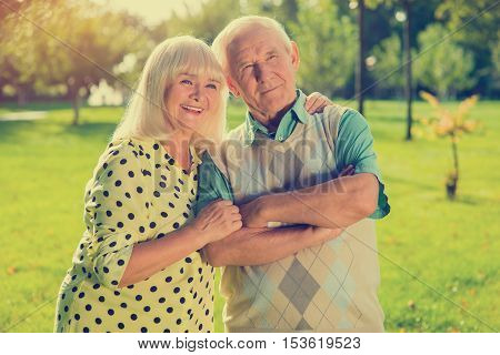 Elderly couple on park background. Man and smiling woman. Years go but feelings remain. Trust and devotion.