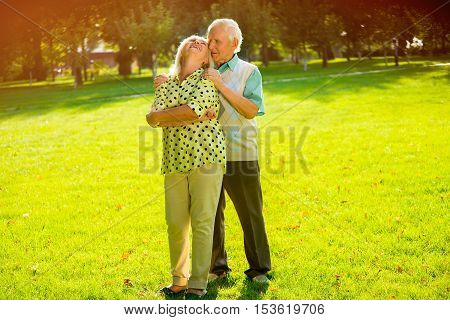 Couple of seniors outdoor. Man standing and hugging woman. Find the greatest happiness. Live and love each other.