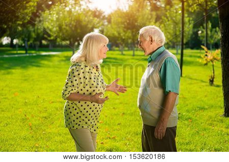Elderly couple outdoors. Woman smiling and gesturing. Build trust and understanding. Conversation with husband.