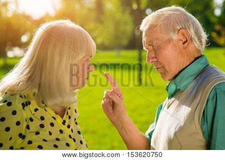 Man points finger at woman. Old grumpy couple. Difficulties in relationships. You don't understand me.