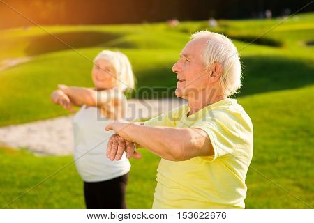 Senior man does exercise. Elderly guy outdoors. How to strengthen the organism. Way to health.