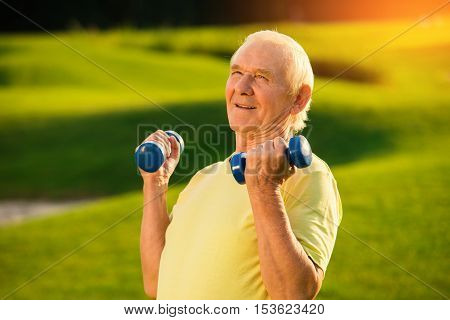 Elderly man holding dumbbells. Smiling old male outdoor. Mind of the champion. You can achieve all goals.