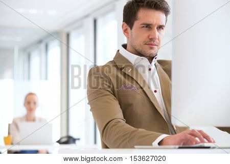 Confident young businessman using computer in office with female colleague in background