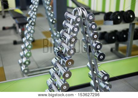 black dumbells over background in sports hall