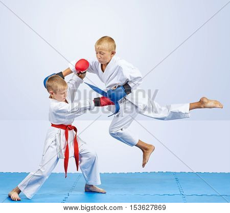 Two karateka with overlays on the hands are training punch in jump and block