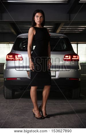 Beautiful confident young businesswoman standing near her car on underground parking