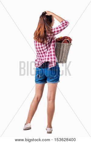 Back view of woman with  basket of dirty laundry. girl is engaged in washing. Rear view people collection.   Girl in shorts and shirt holding a basket of laundry and the second arm straightens hair.